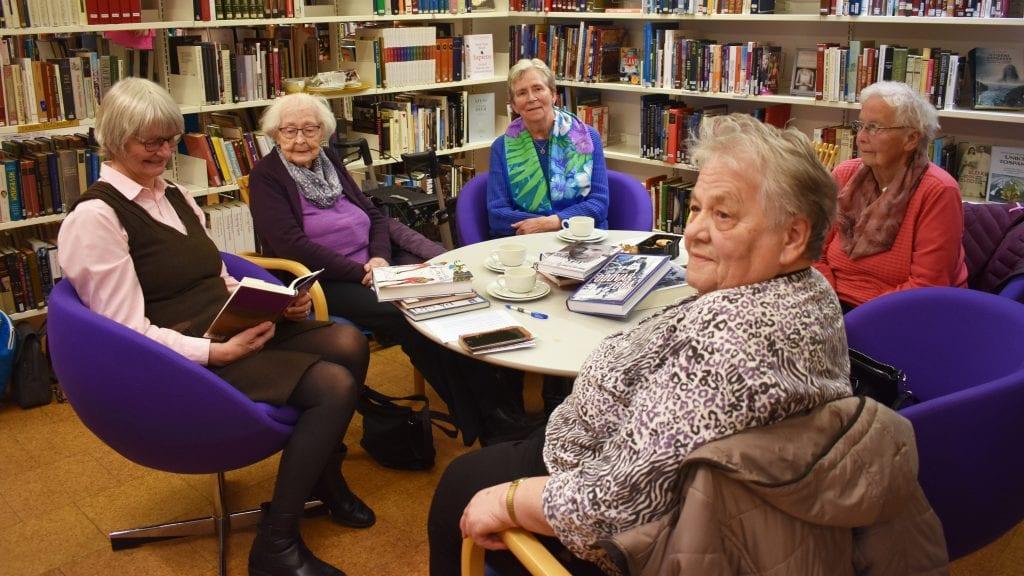 SOSIAL MØTEPLASS: Onsdagene på biblioteket er koselig for Britt Steien Rasmussen (lesende), Halldis Strypet, Anna Tronsli, Gerd Ligård og Gudrun Måntrøen. Foto: Torstein Sagbakken.
